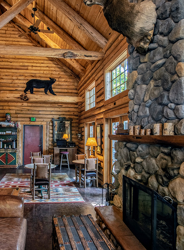 A picture of the grand lodge lobby with river-rock fireplace and two story lodge-pole gable style roof with local wildlife taxidermy